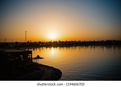 Calm tropical beach, sea or ocean water coast, of seaside resort with dark silhouettes of palm trees during sunset or sundown in evening dusk on clear, grey sky background. Idyllic summer vacation