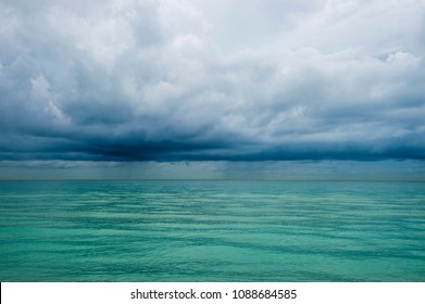 Calm tropical turquoise sea under darkening storm storm clouds on the horizon