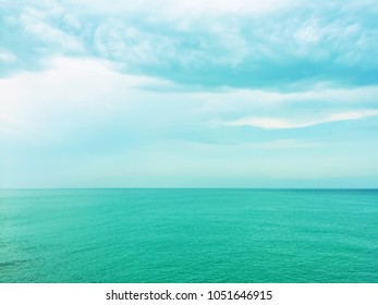 Calm turquoise sea, with light coming through the clouds.