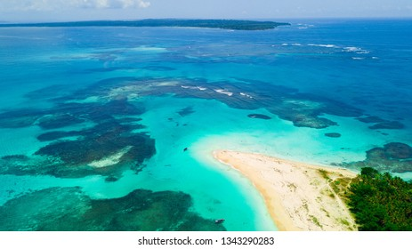 Calm turquoise water and coral reef surrounding the empty beach of a secluded Caribbean island in Panama.