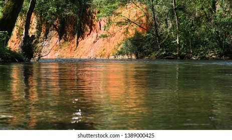 calm water flowing past an ochre colored cliff