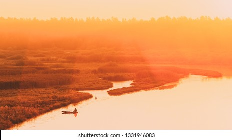 Calm Water Of Lake, River and rowing fishing boat at beautiful sunrise in autumn morning. Fisherman is in the boat