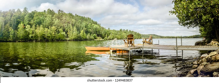 Calm water of lake in summertime with wooden pier and chair on deck in sunlight, Canada