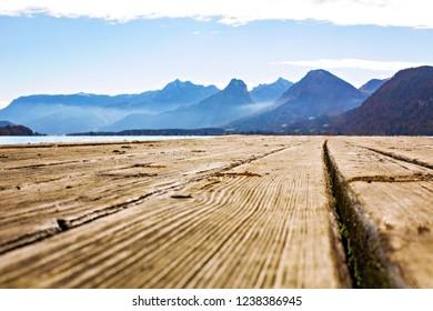 Calm water lake wood dock, mountains view Austria.