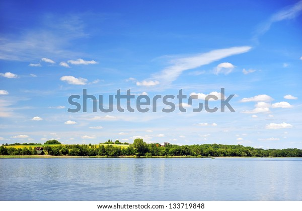 calm water of  lake, woods on other side and  blue sky. landscape