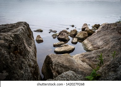 Calm water peaceful and tranquil scene with rocks and stones at the waters edge.