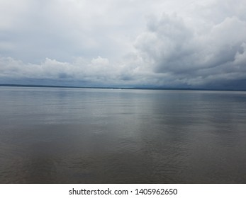 calm water in river or lake and white clouds