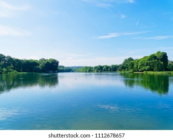 The calm water of a tree lined lake reflects the summer sky and the trees around its shores