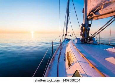 The calm water. White yacht sailing at sunset. A view from the deck to the bow, mast and the sails. Baltic Sea, Latvia