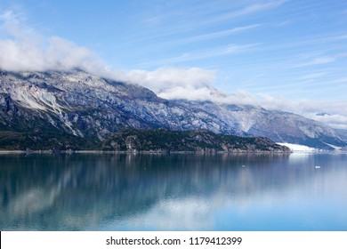 Calm waters with reflections of Glacier Bay coastline, the national park in Alaska.