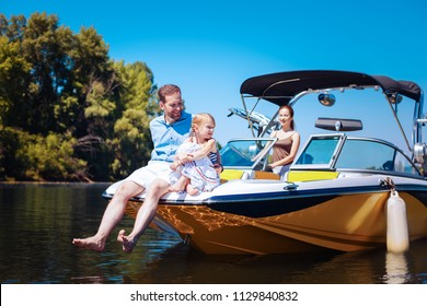 Calm weekend. Pleasant young family relaxing on a motorboat while petite little girl and her father sitting on the bow of the boat and the mother sailing