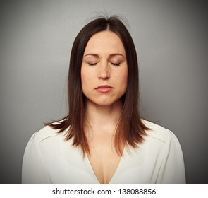 calm woman with closed eyes over grey background