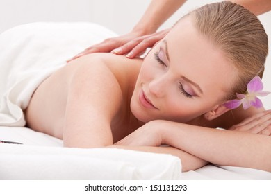 calm woman during luxurious procedure of massage over white