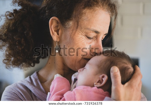 Calm woman embracing and kissing newborn baby with great love.