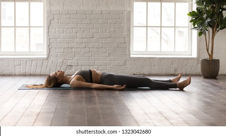 Calm woman in grey sportswear, pants and bra practicing yoga, lying in Savasana, Dead Body pose on mat, beautiful girl resting after working out at home or in yoga center with white walls