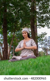 A calm woman just finished meditation in the trees