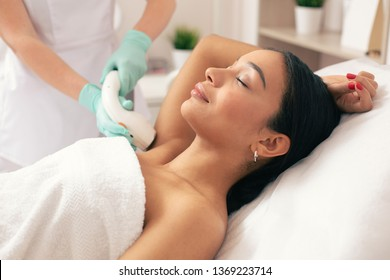 Calm woman lying with her eyes closed and having laser hair removal with a vacuum suction on her armpit