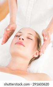 Calm woman receiving reiki treatment in the health spa