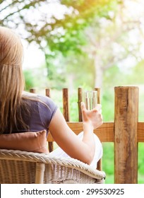Calm woman relaxing outdoors, back side of female sitting on the chair on terrace, drinking water and enjoying beautiful nature view