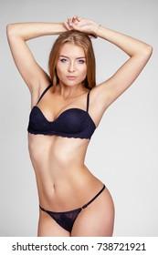 Calm young blonde woman posing in black bikini over white background