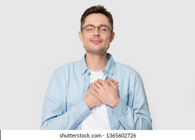 Calm young Caucasian male in glasses isolated on grey studio background hold hands on chest close to heart feel grateful, thankful European man in appreciation thanking fate. Gratitude concept