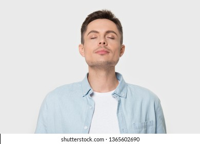 Calm young Caucasian male isolated on grey studio background enjoy pleasant smell or fragrance, relaxed European man in shirt breath deep, feel mindful inhaling fresh air. Stress free concept