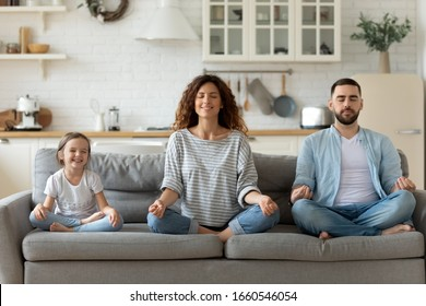 Calm young family with little daughter sit on couch practice yoga together, happy parents with small preschooler girl child rest on sofa meditate relieve negative emotions on weekend at home