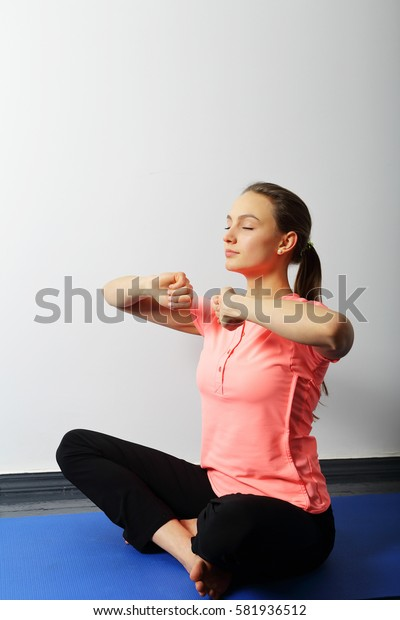 Calm young girl sitting in a yoga pose with hands near his chest, eyes closed