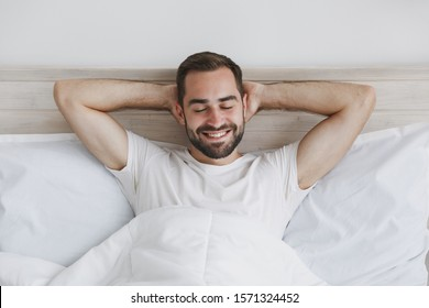 Calm young handsome bearded man lying in bed with white sheet pillow blanket in bedroom at home. Smiling beauty male spending time in room. Rest relax good mood lifestyle concept. Mock up copy space