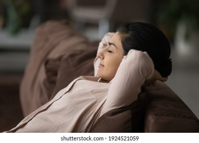 Calm young Indian woman relax on couch at home sleep or take nap relieving negative emotions. Relaxed happy millennial mixed race female rest on sofa daydream or doze. Peace, stress free concept.