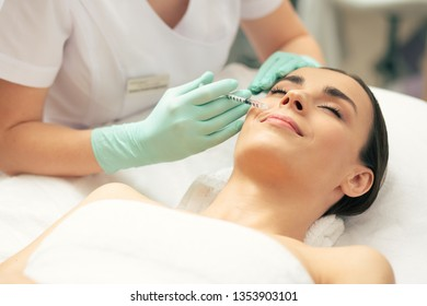 Calm young lady lying with her eyes closed and smiling while professional cosmetologist making an injection with vitamins