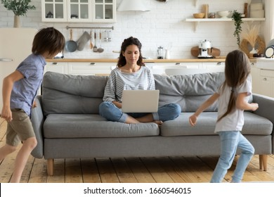 Calm young mother or nanny sit on couch working on laptop, little kids play around, peaceful mom relax on sofa use modern computer distracted from noise, parenting, upbringing concept