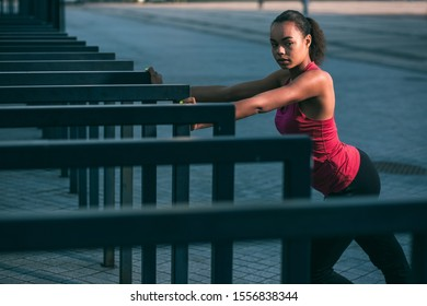 Calm young sportswoman standing outdoors with hands on the banister and looking away