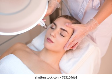Calm young woman is getting anti-aging rejuvenation procedure at beauty salon. Beautician hands holding tool under her face. Top view