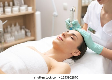 Calm young woman having her eyes closed while professional cosmetologist conducting dermabrasion procedure on her face
