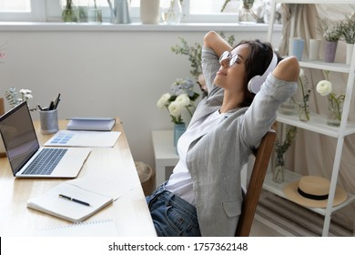 Calm young woman in headphones relax in chair at workplace distracted from computer work listen to music, happy female in headset enjoy good quality sound in earphones, rest at workspace at home
