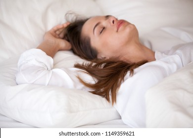 Calm young woman resting in cozy bed on white soft pillows under linen sheets