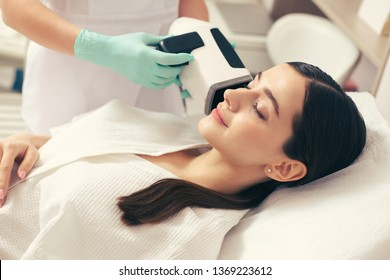 Calm young woman smiling with closed eyes while beautician in rubber gloves holding skin analysis camera near her face