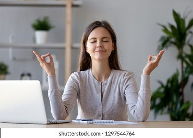 Calm young woman worker taking break doing yoga exercise at workplace, happy mindful female student meditating at home office desk feel balance harmony relaxation, stress relief zen at work concept