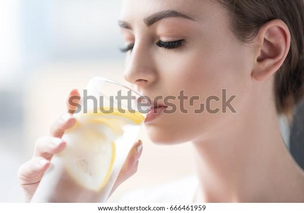 レモン水を飲んで元気を取り戻す若い女性