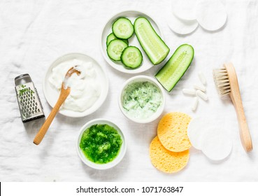 Calming cucumber yogurt mask. Ingredients for homemade cucumber face mask-cucumber, natural yogurt, probiotic capsule, sponges, brush on white background, top view. Flat lay
