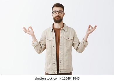 Calming down with yoga. Portrait of relieved peaceful good-looking urban guy in jacket with long sick beard closing eyes spreading hands in zen gesture meditating to restore peace and patience