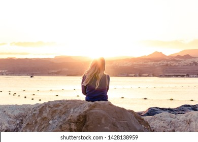 calming romantic and atmospheric photography of sitting girl back to camera on city Red sea waterfront district for walking and enjoy by beautiful bright sunset view