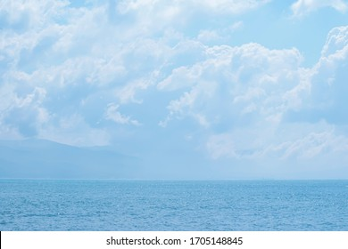Calming summer natural marine blue background with sunbeams. Sea and sky with white clouds. Copy space, summer vacation concept