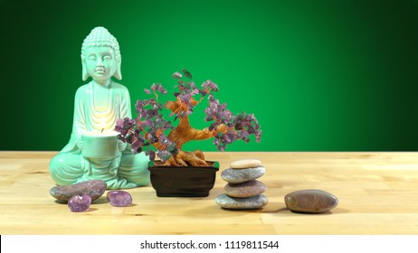 Calming zen interiors table setting with buddha statue holding burning candle, crystals, rocks against green background with copy space.