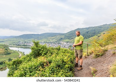 Calmont Climbing, Bremm, Mosel, Germany, september 15, 2013: A male hiker stands on a path between the rows of grapevines and overlooks the Valley and the river