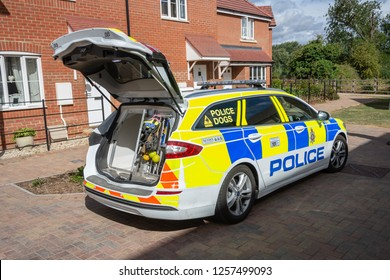 Calne, Wiltshire, UK - July 28 2018 A police estate car specialized for the transport of police dogs has its boot open displaying kenneling and equipment while the dog and handler are on a search