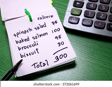 Calorie counting on a paper with calculator. Diet and weight control concept