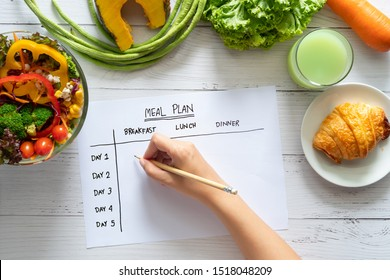 Calories control, meal plan, food diet and weight loss concept. top view of hand filling meal plan on weekly table with salad and fresh vegetable on dining table - Shutterstock ID 1518048209