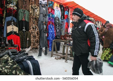 Calugareni, Romania, December 20, 2009: A young man is looking at different products in the animal market in Calugareni.